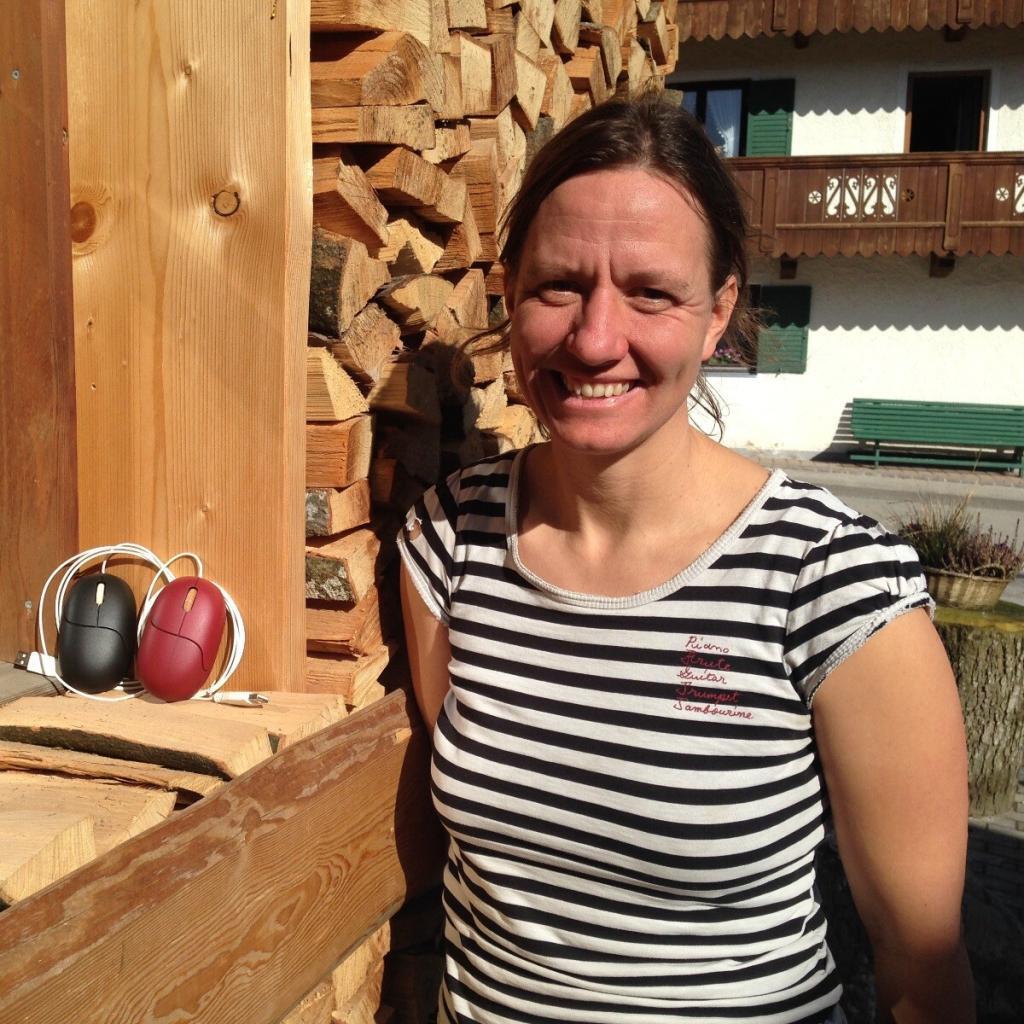 Susanne Jordan die Gründerin von Nager IT steht neben einer Wand aus Holz